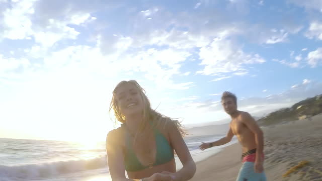 MS DS SLO MO Selfie shot of young couple in bathing suits on beach with beautiful clouds and sunset, golden hour with Girl is spinning around having fun at Santa Monica  / Venice, California, United States