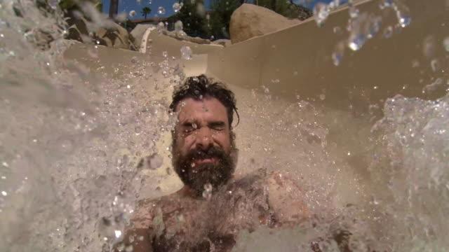 selfie video of bearded hairy dude riding water slide - acquascivolo video stock e b–roll