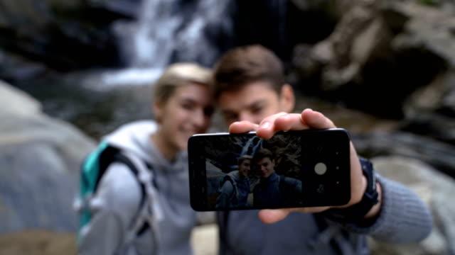 stockvideo's en b-roll-footage met selfie met beste vriend voor bos waterval-wandelen en gezonde levensstijl - zelfportret fotograferen