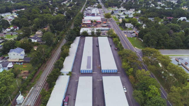 self-storage hangars in the industrial zone in long island, new york state, usa. aerial drone video with the forward, slow ascending and tilting-down camera motion. - self storage stock videos and b-roll footage