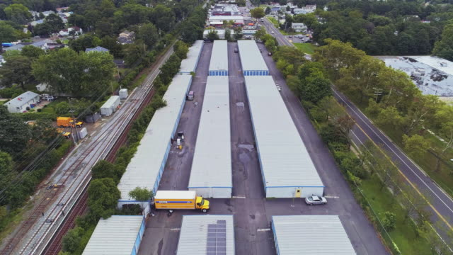 self-storage hangars in the industrial zone in long island, new york state, usa. aerial drone video with the forward camera motion. - self storage stock videos and b-roll footage