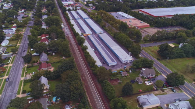 self-storage hangars in the industrial zone in long island, new york state, usa. aerial drone video with the orbit camera motion. - self storage stock videos and b-roll footage