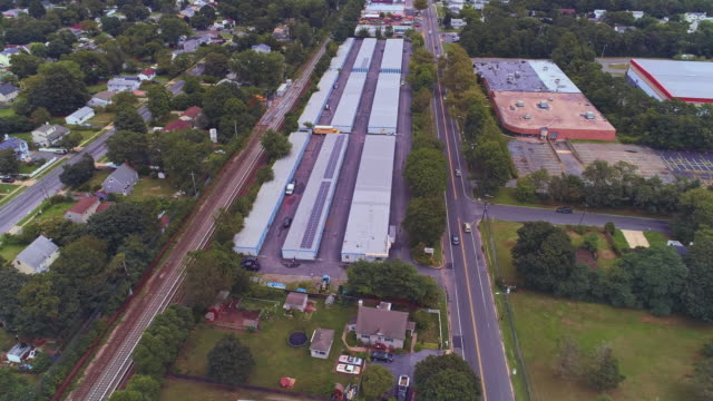 self-storage hangars in the industrial zone in long island, new york state, usa. aerial drone video with the orbit camera motion. - self storage video stock e b–roll