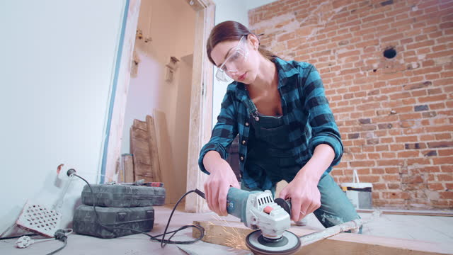 vídeos de stock e filmes b-roll de self-sufficient woman doing men's work in new apartment - broca