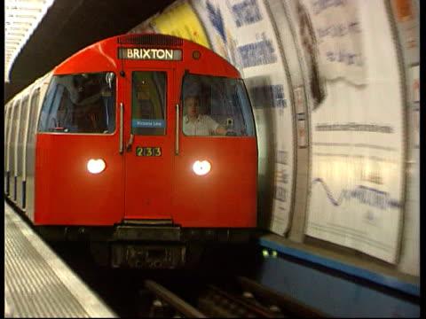 sell off/expansion; lib england: london: int/on board tube train track forward thru tunnel into station 'brixton' tube train towards into station as... - ランベス点の映像素材/bロール
