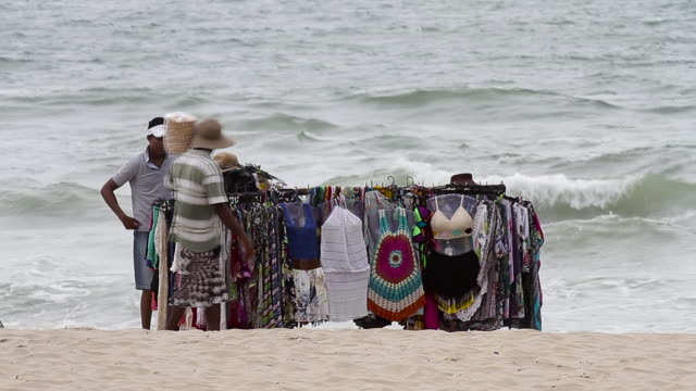 Seller of clothes and peanuts stop to chat excitedly on the beach