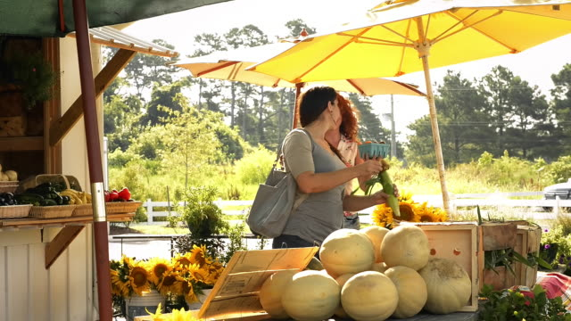 Seller showing produce to woman at farm stand