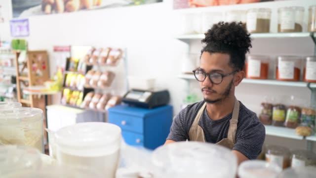 vídeos de stock, filmes e b-roll de vendedor que usa o smartphone para verific produtos em uma loja natural dos produtos - vendor
