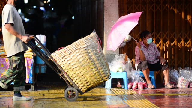 a seller with an umbrella sits in front of pak klong talad market entrance with buyers walking by. - bangkok stock videos & royalty-free footage