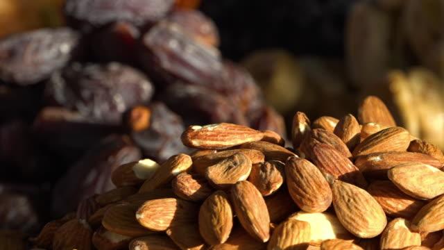 vidéos et rushes de selling dried fruits and nuts on a market - raisin sec