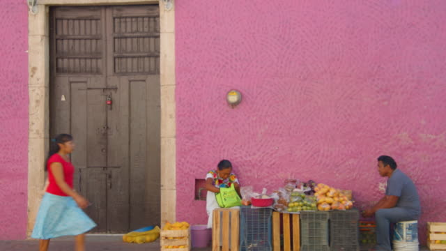 vídeos de stock e filmes b-roll de selling vegetables on the street in front of a pink wall. mexico iconic image - latino americano