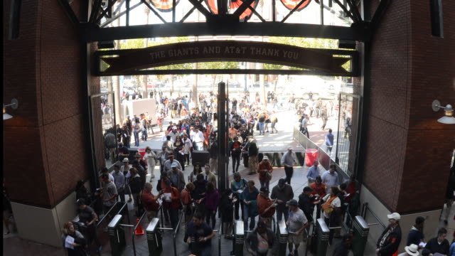 a sell-out crowd for the san francisco giants day game go through turnstiles at the main entrance to the at and t park in san fransisco, california. - building entrance stock videos & royalty-free footage