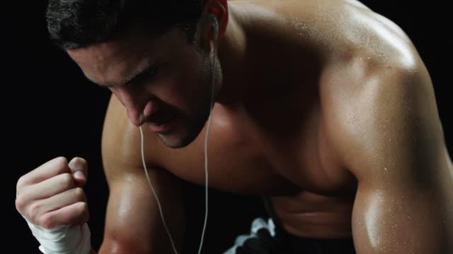 vidéos et rushes de ms tu semi dressed athlete sitting and flexing arm muscles in studio - personne sportive