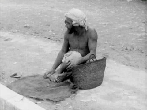1934 b/w ms ha semi dressed man sitting on dirt with basket and rag / rabat, morocco - 1934 bildbanksvideor och videomaterial från bakom kulisserna