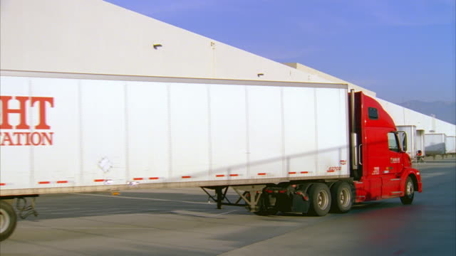 vídeos de stock, filmes e b-roll de ws pan semi tractor-trailer driving away from loading dock at warehouse exterior / lebec, california, united states - carregamento frete