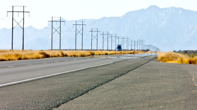 semi-camion sull'autostrada deserto - traliccio elettrico video stock e b–roll