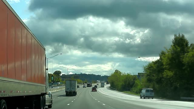 Semi truck on US highway under cloudy sky