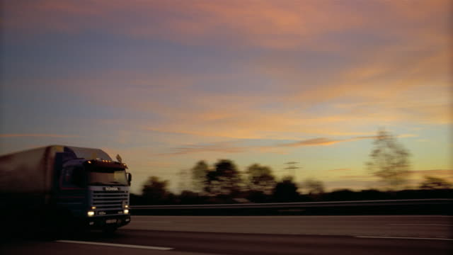 a semi truck travels down a highway. - lastzug stock-videos und b-roll-filmmaterial