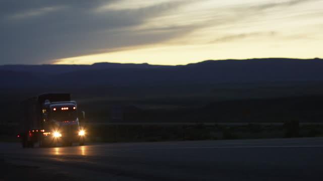 vidéos et rushes de un semi-camion avec des phares sur des disques dans le désert élevé du colorado occidental au crépuscule avec la silhouette du monument national du colorado dans l'arrière-plan - phare avant de véhicule