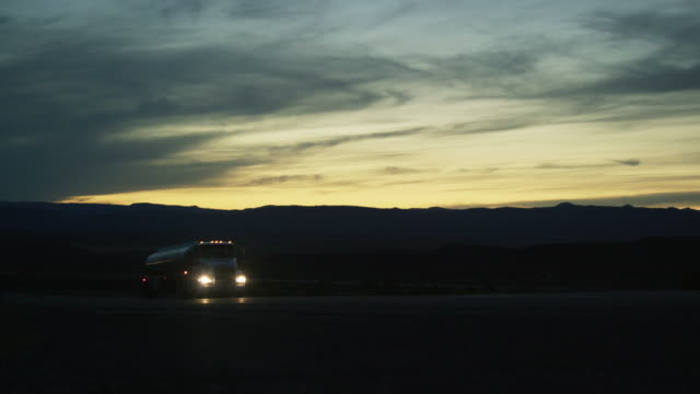 a semi truck with headlights on drives in the high desert of western colorado at dusk - articulated lorry stock videos & royalty-free footage