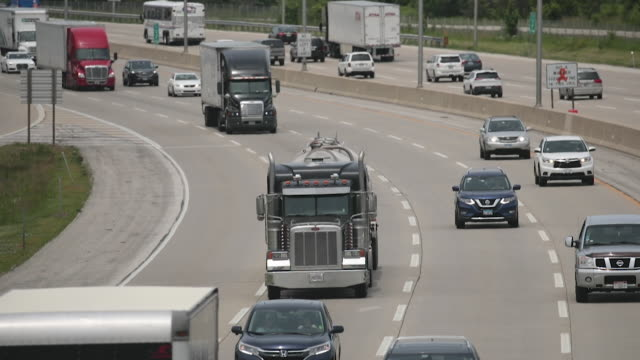 semi trucks travel along i94 on june 21, 2019 near lake forest, illinois. the trucking industry in 2019 has experienced a drop in demand from 2018... - major road stock-videos und b-roll-filmmaterial