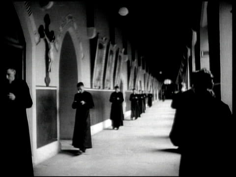 vídeos de stock e filmes b-roll de ws seminary students in clerical clothing walking in hallway while reading prayer walking students in library ms student taking book from arts... - 1944