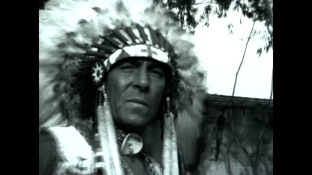 A Seminole Native American wearing a headdress plays the drums and chants