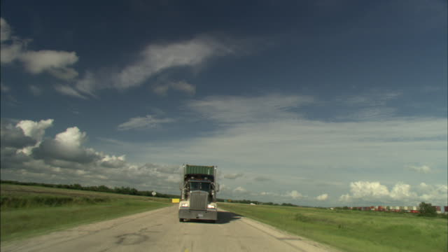 A semi-truck drives along a rural highway.