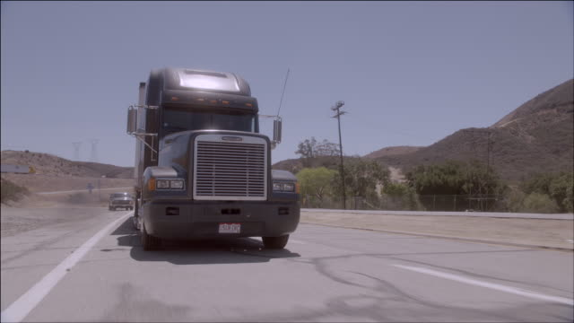 TS A semi-truck driving swiftly down a desert road / Los Angeles, California, United States