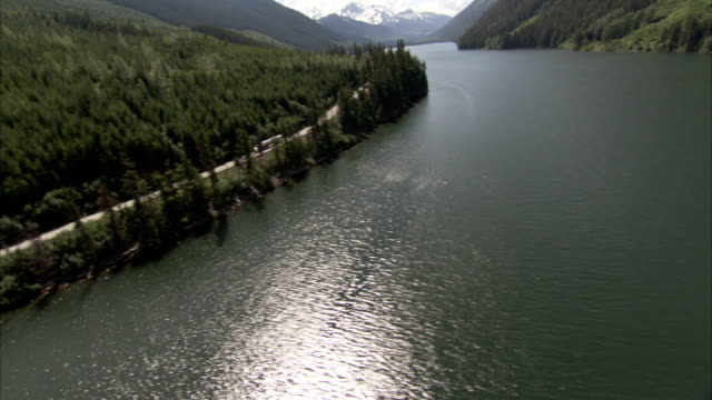 a semi-truck moves along an evergreen-lined lakeshore in the canadian rocky mountains. available in hd. - lakeshore stock videos & royalty-free footage