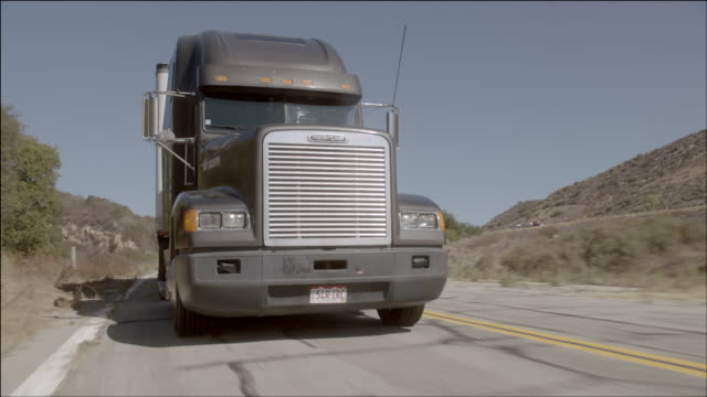 TS A semi-truck moving swiftly down desert road / Los Angeles, California, United States