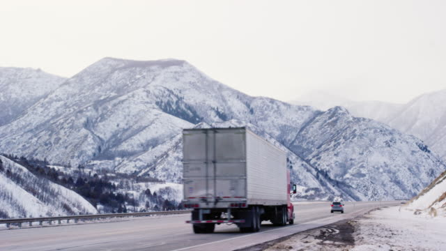 semi-trucks and other vehicles drive along a snowy interstate in utah surrounded by snow-covered mountains on an overcast day - heavy goods vehicle stock videos & royalty-free footage