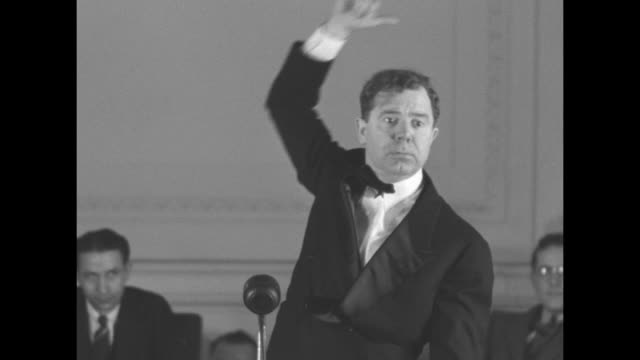 """sen. huey long, dressed in a tuxedo, gestures extravagantly as he delivers speech to the """"little congress"""" club detailing his """"share the wealth""""... - ポピュリズム点の映像素材/bロール"""