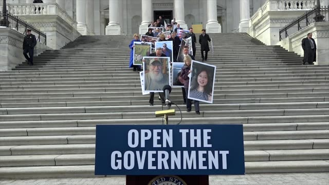 senate democrats descend east front steps of the us capitol building outside the senate chamber holding pictures of those affected by the longest... - government shutdown stock videos & royalty-free footage