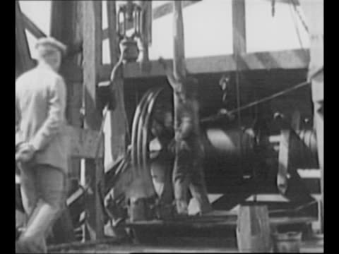 senator burton k. wheeler / workers on oil rig / oil spurts up derrick / oil magnate edward l. doheny decars, walks / doheny shakes hands with man,... - former stock videos & royalty-free footage
