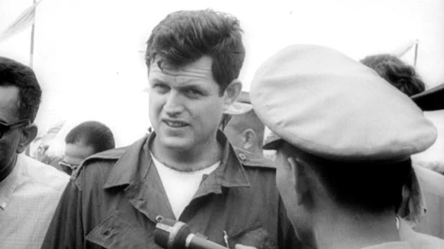 Senator Edward Kennedy of Massachusetts and other US Congressmen visit South Vietnam refugee camps / smiling refugee children hold American and...