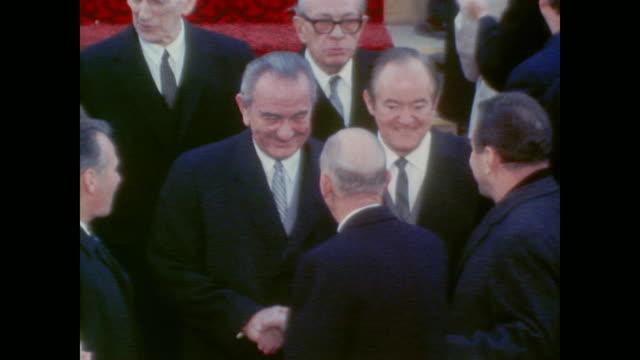Senator Everett Dirksen greets President Lyndon Johnson and Vice President Hubert Humphrey as they find their seats before inauguration