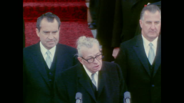 Senator Everett Dirksen makes announcement as the inauguration party stand for song
