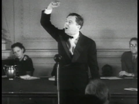 vídeos de stock, filmes e b-roll de senator huey long dressed in tuxedo standing behind microphone gesturing w/ raised fist pointing finger multiple images of huey gesturing montage. - 1933