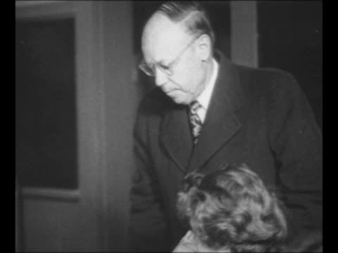vidéos et rushes de senator robert taft smiles outside polling place, wearing fedora and overcoat / taft signs in at polling place / montage he exits voting booth, puts... - couvre chef