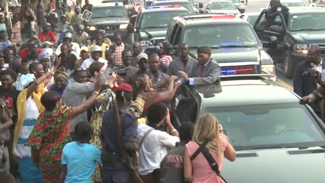 vídeos de stock, filmes e b-roll de senegal's president abdoulaye wade paraded around the capital in a convoy on tuesday standing in an openroofed car waving to onlookers as campaign... - senegal
