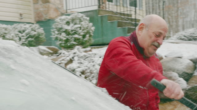 senior 69-years-old man cleaning car from snow in the winter. - 65 69 years stock videos & royalty-free footage