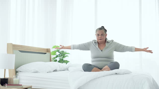 senior active southeast asian woman wearing warm cloth cross-legged sitting,  practicing yoga without exercise equipment after waking up in morning with feeling refreshment on white bed in the apartment. concept of active lifestyles of senior people. - cross legged stock videos & royalty-free footage