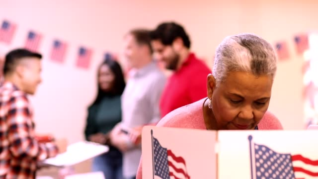 senior adult, african descent woman votes in usa election. - voting stock videos & royalty-free footage