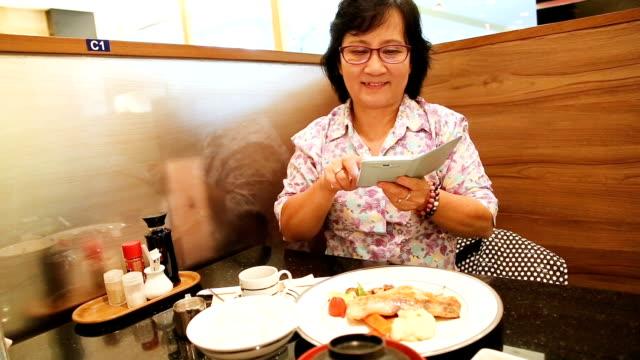 シニア大人のアジアの女性はスマート フォンによるにおいてドメイン外の写真を撮るします。 - タイ人点の映像素材/bロール