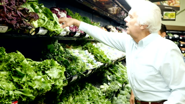 Senior adult Caucasian man shopping in produce section of local supermarket