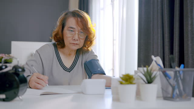 senior adult checking blood pressure recording her blood pressure numbers in notebook at home. - human limb stock videos & royalty-free footage
