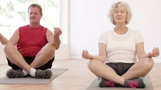 Senior Adult Couple doing Lotus Position in Yoga Class