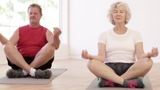 Senior Couple adulte faisant la Position du Lotus dans le cours de Yoga