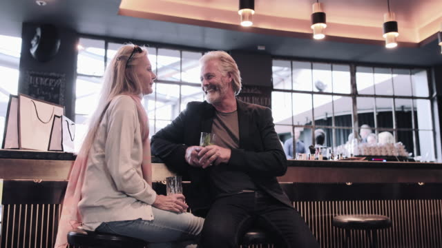 vídeos de stock e filmes b-roll de senior adult couple drinking in hotel bar - elegância
